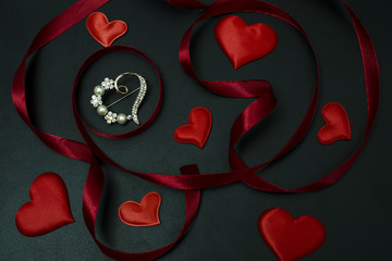 Wall Mural - brooch heart among ribbon and hearts on a black background