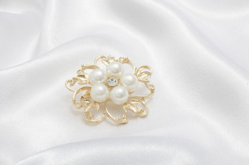 Wall Mural - gold brooch flower with pearl on silk background
