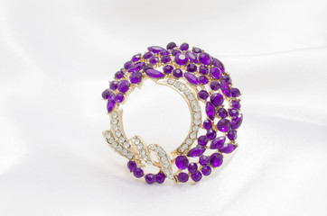 Wall Mural - golden round brooch with purple diamonds on white silk