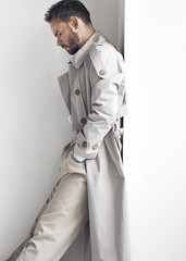 Fashion portrait of man with dark beard and hair, weared in light trench coat and beige pants.