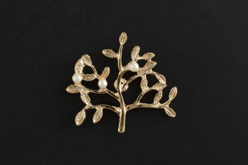 Wall Mural - brooch golden tree with pearls isolated on a black background
