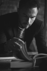 Black and white portrait of handsome stylish man in jacket. Man reading the book.