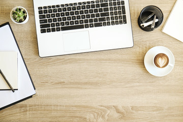 Minimalistic flat lay composition with black & white laptop computer keyboard, cup of coffee with heart shape latte art on wooden desk background. Close up, top view, copy space. Creative workspace.