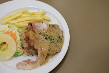 Grilled chicken and bacon with black pepper sauce, carrot, pineapple and french fries serve on white plate - food concept.