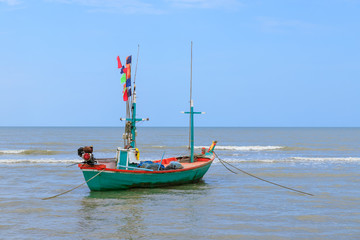Traditional fishing boat tied with rope in sea near beach