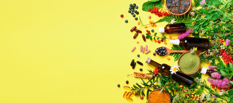 Holistic medicine approach. Healthy food eating, dietary supplements, healing herbs and flowers. Turmeric, dried lavender, spirulina powder in wooden bowls, fresh berries, omega acid capsules