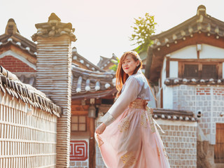 travel and tourist asia concept from beautiful woman in korea traditional cloth (hanbok) relax, take picture in vintage town with rim light and soft focus background