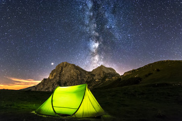 A Camping Tent in the Peak of Mountain with Corno piccolo, Corno Grande and Milky Way Background. In Prati di Tivo - Abruzzo - Italy