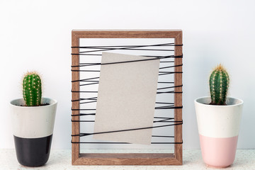 Wooden frame with a gray mockup with two cactuses in pots on both sides standing on a terrazzo table against a white wall