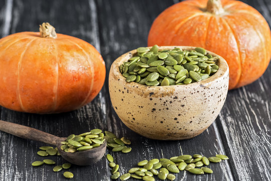 Bowl with raw pumpkin seeds on a rustic black table. Small orange pumpkins. selective focus