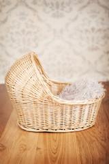 Wicker bassinet against a vintage background