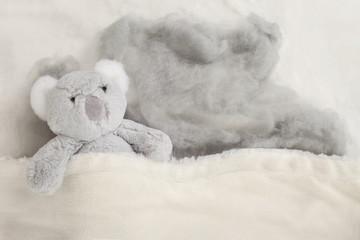 Grey teddy bear in white fluffy blanket