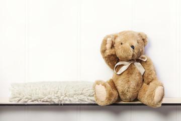Teddy bear on shelf with sheepskin