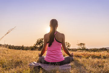 Young beautiful woman practicing Yoga outdoor in nature during sunset