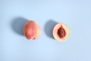 Ripe beautiful peach whole and divided in half. Visible the stone is