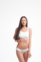 Slim young woman in underwear on white background