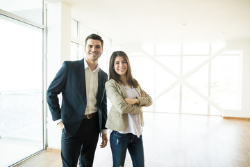 Smiling Real Estate Agents Standing In New Apartment