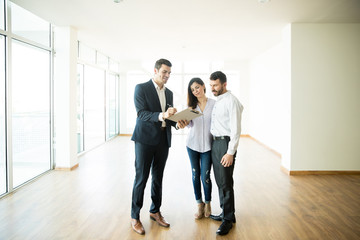 Realtor Explaining Agreement To Couple In New Apartment
