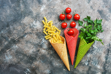 Pasta, cherry tomato and parsley in colored wafer cone on a rustic abstract background. View from above, flat lay