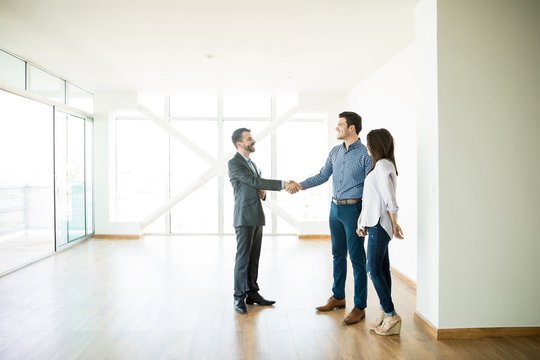 Estate Agent Greeting Couple During Visit To New Home