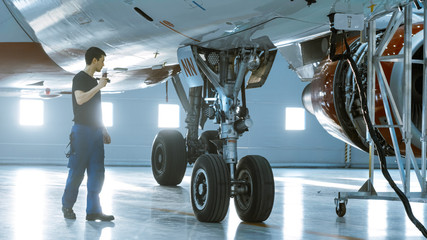 In a Hangar Aircraft Maintenance Engineer/ Technician/ Mechanic Visually Inspects Airplane's Chassis.