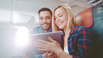 On a Board of Commercial Airplane Beautiful Young Blonde with Handsome Hispanic Male Use Tablet Computer and Smile. Sun Shines Through Aeroplane Window.