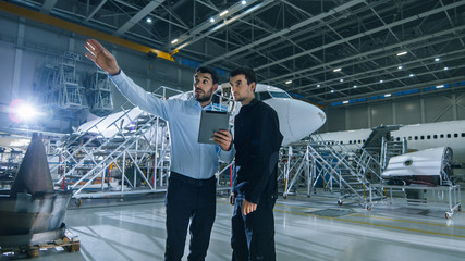 Aircraft Maintenance Worker and Engineer having Conversation. Holding Tablet and Points with His Hand.