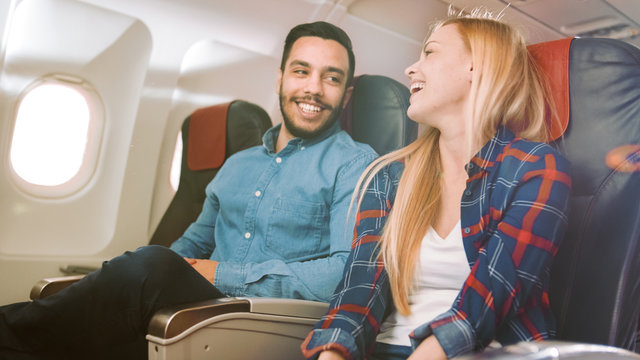 On a Commercial Plane Flight Handsome Hispanic Man Tells Funny Story to His Beautiful Blonde Girlfriend. Both Laugh. They Travel in New Airplane, with Sun Shining Through the Window.