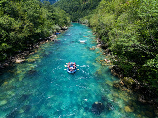 Rafting on the beautiful mountain river. Aerial view of rafting boat on amazing blue river