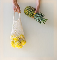 Hands holding mesh shopping bag with lemons and ananas