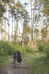 the girl is walking with a bicycle and a guitar in the woods