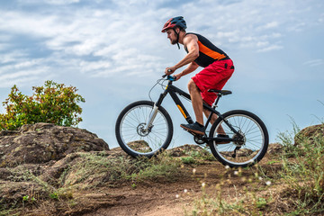 Cyclist in a helmet and with a backpack riding down the rock on a mountain bike, an active lifestyle.