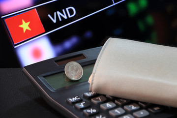 Two hundred Vietnam Dong coin on obverse (VND) on black calculator and wallet with digital board of currency exchange money background, the concept of finance.