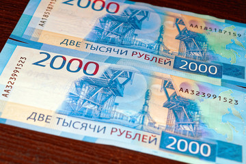 Russian two thousandth notes close-up against the background of a dark wooden table
