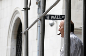 A man smokes a cigar on Wall St. outside of the NYSE in New York