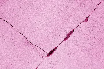 Cracked cement wall in pink color.