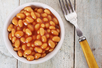 baked beans in tomato sauce in white  dish