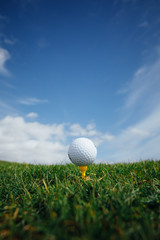 Poster Golf golf ball on tee, green grass and blue sky background
