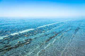 Seascape with coastline. Stone road under water. The sea shore is rocky formation under clear water. The stone is beautiful layers and strips.
