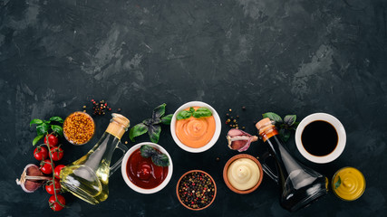 Set of sauces - Ketchup, mayonnaise, mustard, soy sauce, barbecue sauce, pepper and spices. On a black stone background. Top view. Free space for text.