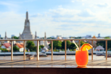 Orange juice and Orange slice with Straw in glass on the rooftop bar and background of Wat Arun. The famous place of Bangkok, Thailand. Bangkok and Wat Arun is the most populated city in Asia.