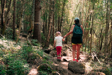 Hiking in the woods. Mother and daughter are walking on a path in a warm sunny forest. Impassable rocky trail. Skule mountain close to Docksta in northern Sweden.
