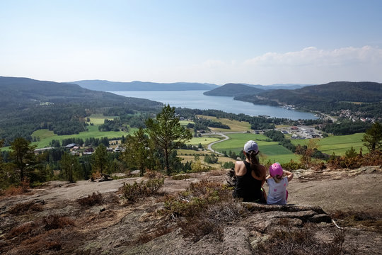 Family travel. Mother and daughter rest from hiking uphill a mountain. Beautiful view of archipelago, mountains, forest and sea. Skule mountain, high coast in northern Sweden.