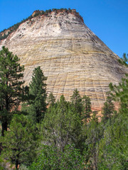 High mountain with striped surface, clear blue sky above and green trees at the bottom, West USA