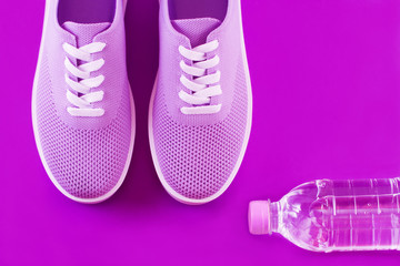Layout on a bright violet background - light purple sneakers and a bottle of water on a purple background with a place for an inscription.