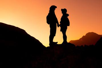 Happy couple on mountain range at sunset landscape. Fann mountains, Tajikistan
