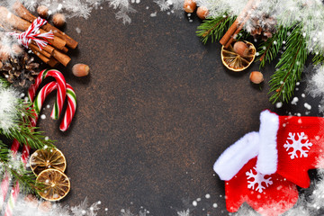 Christmas tree with decorations and mittens on a brown background with space under the text.
