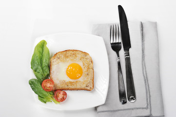 Toast with fried egg on a white plate. On a plate, spinach leaves and cherry tomatoes. Next to the dish there is a napkin and cutlery. White background. Close-up. View from above.