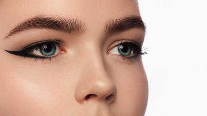 Close up view of blue woman eye with beautiful golden shades and black eyeliner makeup. Classic make up. Perfect brows. Studio shot