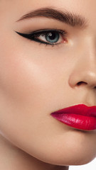 Beautiful woman with bright make up eye with sexy black liner makeup. Fashion big arrow shape on woman's eyelid and pink lips . Chic evening make-up, lipstick